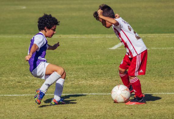 dwaj chłopcy grający w piłkę nożną na boisku